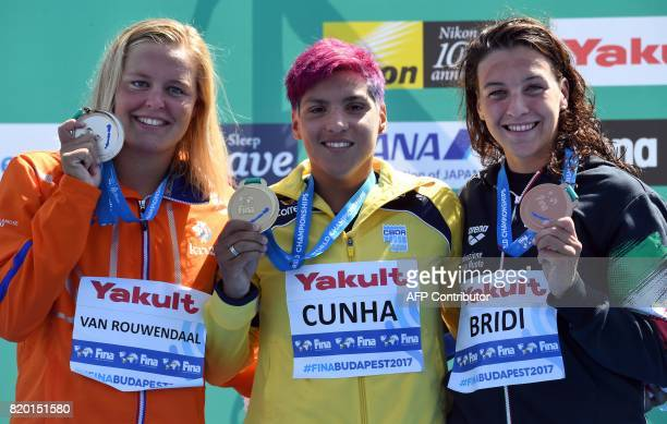 Gold medalist Brazil's Ana Marcela Cunha celebrates her victory with runnerup Sharon van Rouwendaal of The Netherlands and third placed Italy's...