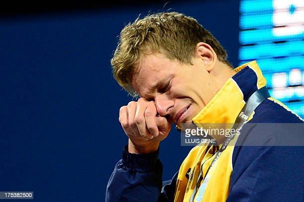 Gold medalist Brazil's Cesar Cielo Filho wipes his tears on the podium during the award ceremony of the men's 50metre freestyle swimming event in the...