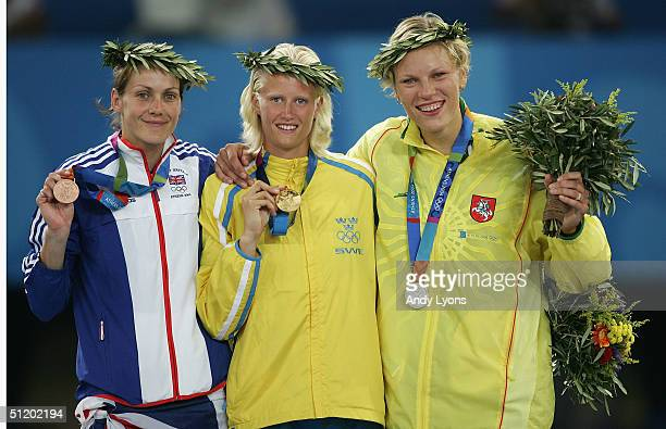 Gold medalist Carolina Kluft of Sweden silver medalist Austra Skujyte of Lithuania and bronze medalist Kelly Sotherton of Great Britain celebrate on...