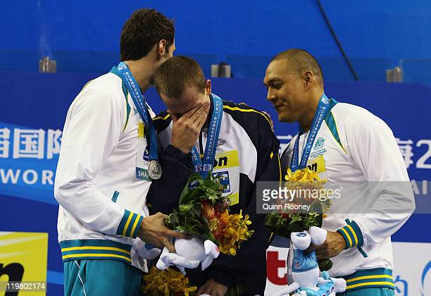 Gold medalist Cesar Cielo Filho of Brazil is consoled by silver medalist Matthew Targett of Australia and bronze medalist Geoff Huegill of Australia...
