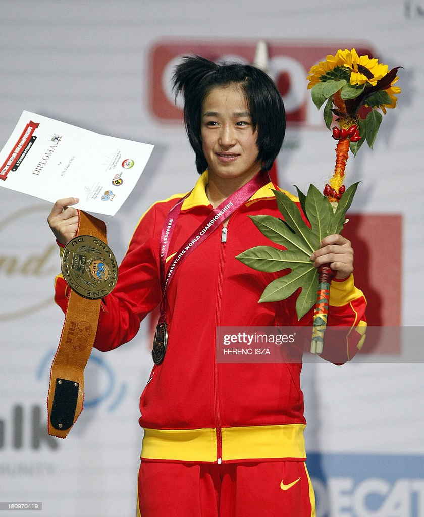 Gold medalist China's Yanan Sun celebrates on the podium of the women's free style 51 kg category of the World Wrestling Championships in Budapest on September 18, 2013. AFP PHOTO / FERENC ISZA