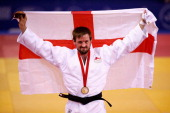 Gold medalist Colin Oates of England celebrates on the podium during the medal ceremony for the Men's 66kg contest at SECC Precinct during day one of...