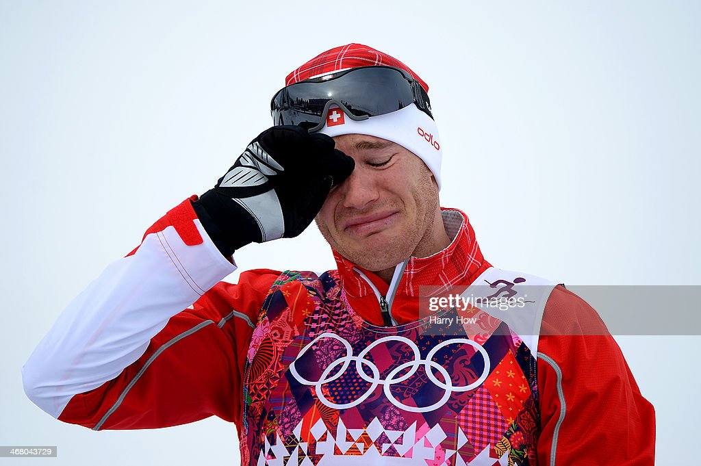 Gold medalist <a gi-track='captionPersonalityLinkClicked' href=/galleries/search?phrase=Dario+Cologna&family=editorial&specificpeople=4779620 ng-click='$event.stopPropagation()'>Dario Cologna</a> of Switzerland celebrates on the podium during the flower ceremony for the Men's Skiathlon 15 km Classic + 15 km Free during day two of the Sochi 2014 Winter Olympics at Laura Cross-country Ski & Biathlon Center on February 9, 2014 in Sochi, Russia.