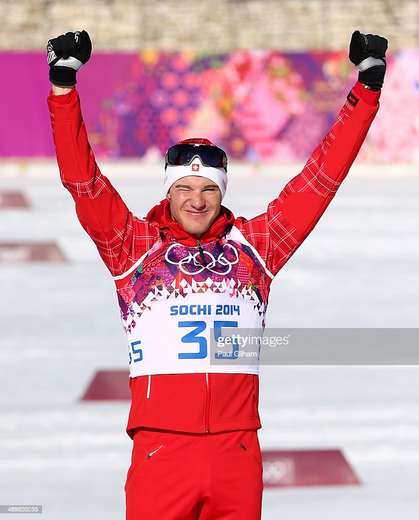 Gold medalist <a gi-track='captionPersonalityLinkClicked' href=/galleries/search?phrase=Dario+Cologna&family=editorial&specificpeople=4779620 ng-click='$event.stopPropagation()'>Dario Cologna</a> of Switzerland celebrates on the podium during the flower ceremony for the Cross Country Men's 15km Classic event during day seven of the Sochi 2014 Winter Olympics at Laura Cross-country Ski & Biathlon Center on February 14, 2014 in Sochi, Russia.