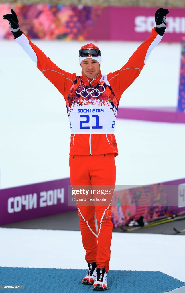 Gold medalist <a gi-track='captionPersonalityLinkClicked' href=/galleries/search?phrase=Dario+Cologna&family=editorial&specificpeople=4779620 ng-click='$event.stopPropagation()'>Dario Cologna</a> of Switzerland stands on the podium during the flower ceremony for the Men's Skiathlon 15 km Classic + 15 km Free during day two of the Sochi 2014 Winter Olympics at Laura Cross-country Ski & Biathlon Center on February 9, 2014 in Sochi, Russia.