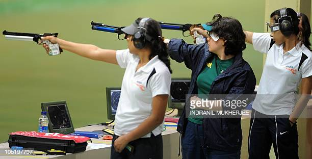 Gold medalist duo Annu Raj Singh and Heena Sidhu of India and silver medalist Dina Aspandiyarova of Australia concentrate before firing in the...