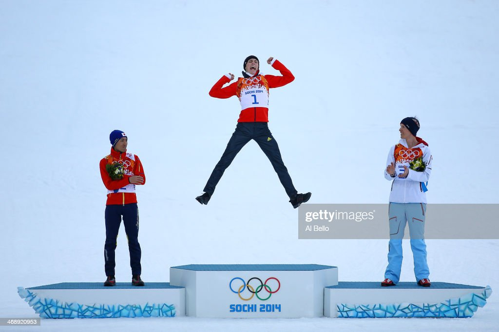 Gold medalist <a gi-track='captionPersonalityLinkClicked' href=/galleries/search?phrase=Eric+Frenzel&family=editorial&specificpeople=4595984 ng-click='$event.stopPropagation()'>Eric Frenzel</a> of Germany jumps in celebration alongside silver medalist <a gi-track='captionPersonalityLinkClicked' href=/galleries/search?phrase=Akito+Watabe&family=editorial&specificpeople=829954 ng-click='$event.stopPropagation()'>Akito Watabe</a> of Japan (L) and bronze medalist Magnus Krog of Norway (R) during the flower ceremony for the Men's Nordic Combined Individual Gundersen Normal Hill and 10km Cross Country on day 5 of the Sochi 2014 Winter Olympics at the RusSki Gorki Nordic Combined Skiing Stadium on February 12, 2014 in Sochi, Russia.