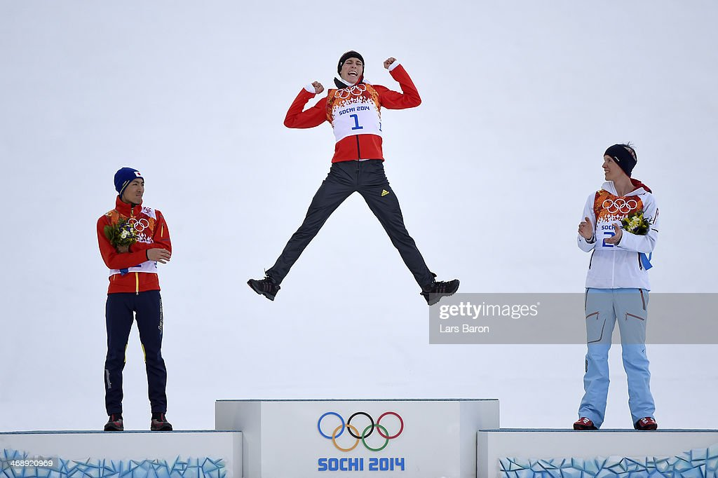 Gold medalist Eric Frenzel of Germany jumps in celebration alongside silver medalist Akito Watabe of Japan (L) and bronze medalist Magnus Krog of Norway (R) during the flower ceremony for the Men's Nordic Combined Individual Gundersen Normal Hill and 10km Cross Country on day 5 of the Sochi 2014 Winter Olympics at the RusSki Gorki Nordic Combined Skiing Stadium on February 12, 2014 in Sochi, Russia.