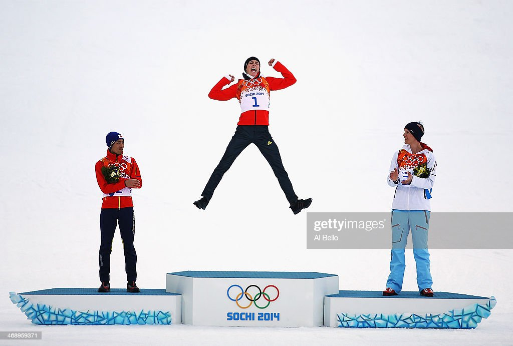 Gold medalist Eric Frenzel of Germany jumps in celebration alongside silver medalist Akito Watabe of Japan (L) and bronze medalist Magnus Krog of Norway (R) during the flower ceremony for the Men?s Nordic Combined Individual Gundersen Normal Hill and 10km Cross Country on day 5 of the Sochi 2014 Winter Olympics at the RusSki Gorki Nordic Combined Skiing Stadium on February 12, 2014 in Sochi, Russia.
