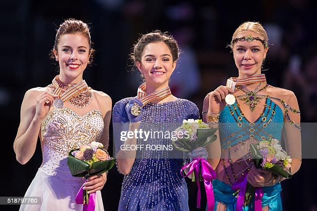 Gold medalist Evgenia Medvedeva (C) of Russia poses for photographs with silver medalist Ashley Wagner of the United States (L)and bronze medalist Anna Pogorilaya of Russia (R) during the victory ceremony for the Ladies competition at the ISU World Figure Skating Championships at TD Garden in Boston, Massachusetts, April 2, 2016. / AFP / Geoff Robins
