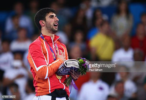 Gold medalist Firdovsi Farzaliyev of Azerbaijan sings the national anthem during the medal ceremony for the Men's Kumite 60kg on day one of the Baku...