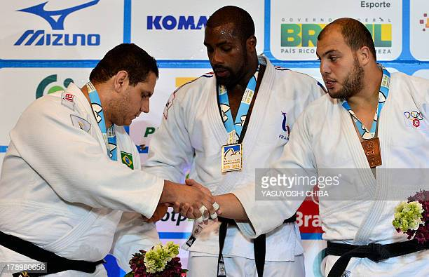 Gold medalist France's Teddy Riner Silver medalist Brazil's Rafael Silva Bronze medalist Tunisia's Faicel Jaballah greet each other during the medal...