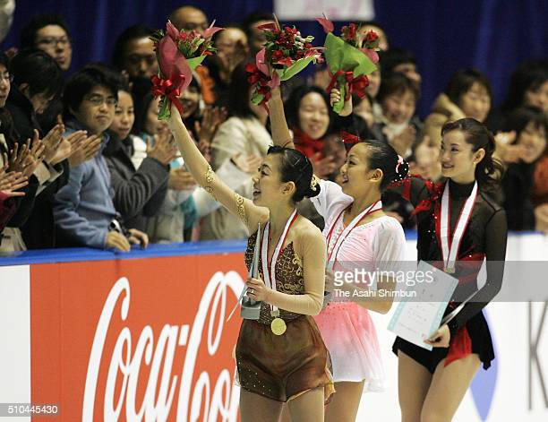 Gold medalist Fumie Suguri silver medalist Mao Asada and bronze medalist Shizuka Arakawa applaud crowd after the medal ceremony for the Women's...