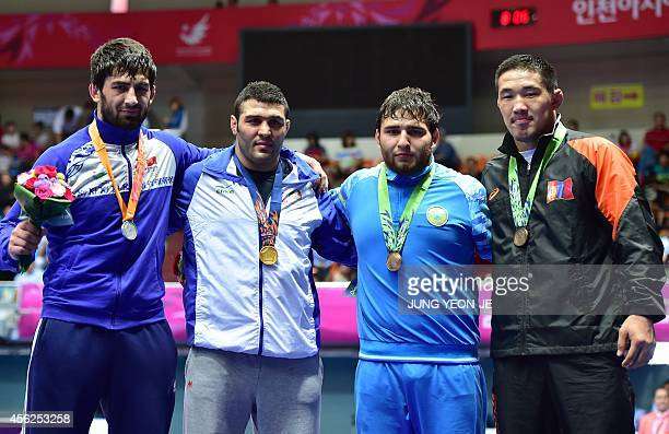 Gold medalist Iran's Reza Yazdani poses with silver medalist Kyrgyzstan's Magomed Musaev and bronze medalists Mongolia's Khuderbulga Dorjkhand and...