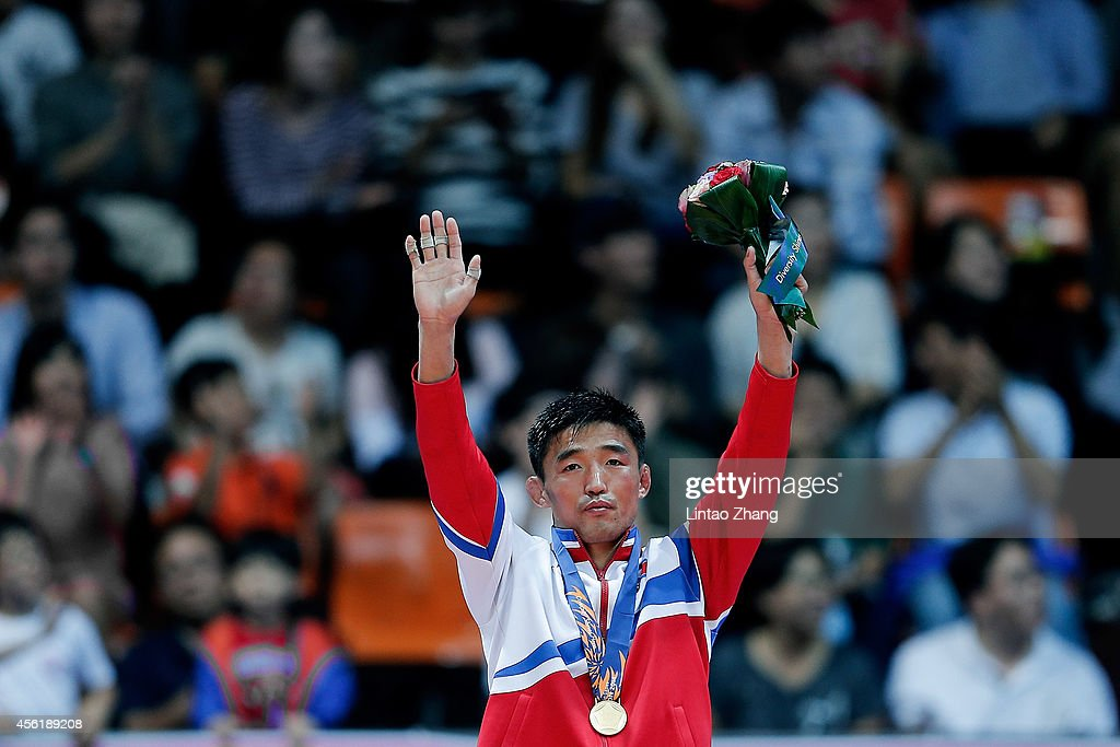 Gold medalist Jong Hakjin of North Korea celebrates during the medal ceremony after Wrestling Men's Freestyle 57 kg Gold Medal Final during day eight of the 2014 Asian Games at Dowon Gymnasium on September 27, 2014 in Incheon, South Korea.