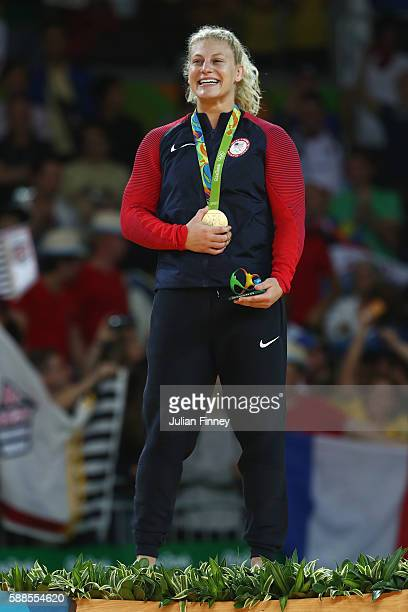 Gold medalist Kayla Harrison of the United States celebrates on the podium after defeating Audrey Tcheumeo of France during the women's 78kg gold...