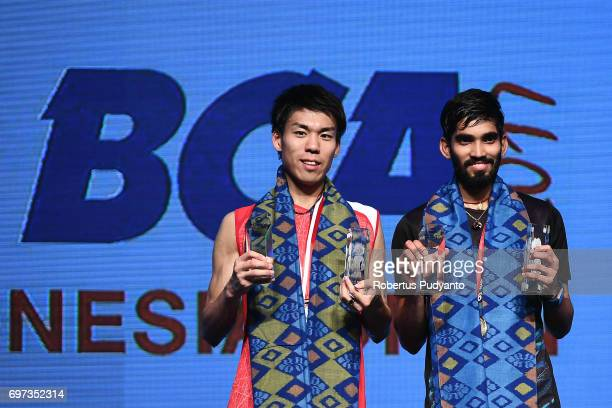Gold medalist Kidambi Srikanth of India and silver medalist Kazumasa Sakai of Japan celebrate on the podium during Men's Single medals ceremony of...