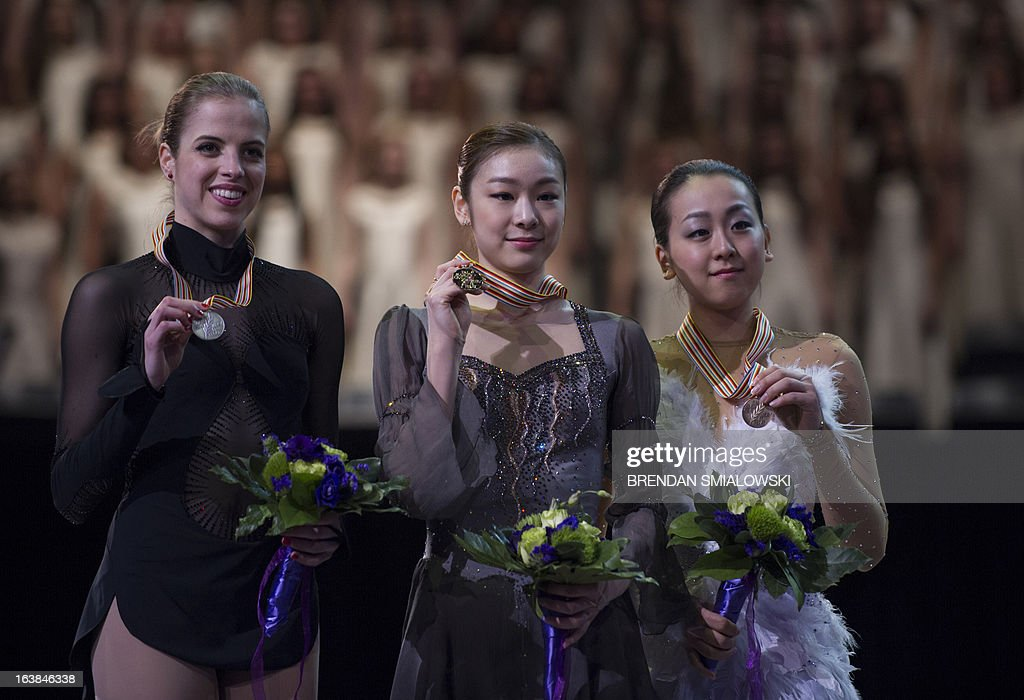 Gold medalist Kim Yu-na (C) from South Korea stands with silver medalist Carolina Kostner (L) of Italy, and bronze medalist Mao Asada of Japan during the victory ceremony for the dance competition at the 2013 World Figure Skating Championships in London, Ontario, March 16, 2013. Reigning Olympic champion Kim Yu-Na won the women's title at the World Figure Skating Championships, taking a runaway triumph in the free skate final. AFP PHOTO / Brendan SMIALOWSKI