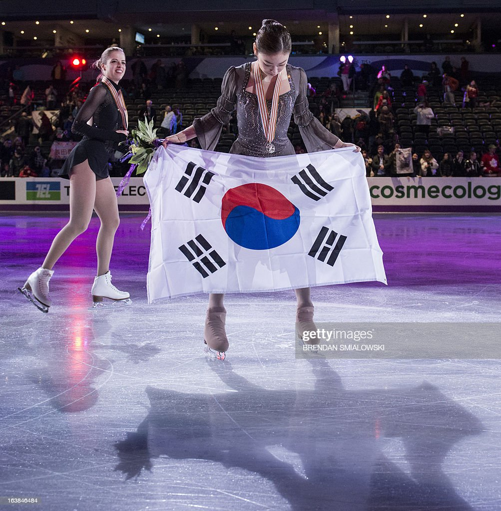 Gold medalist Kim Yu-na of South Korea displays the South Korean national flag during the victory ceremony for the dance competition at the 2013 World Figure Skating Championships in London, Ontario, March 16, 2013. Reigning Olympic champion Kim Yu-Na won the women's title at the World Figure Skating Championships, taking a runaway triumph in the free skate final. AFP PHOTO / Brendan SMIALOWSKI