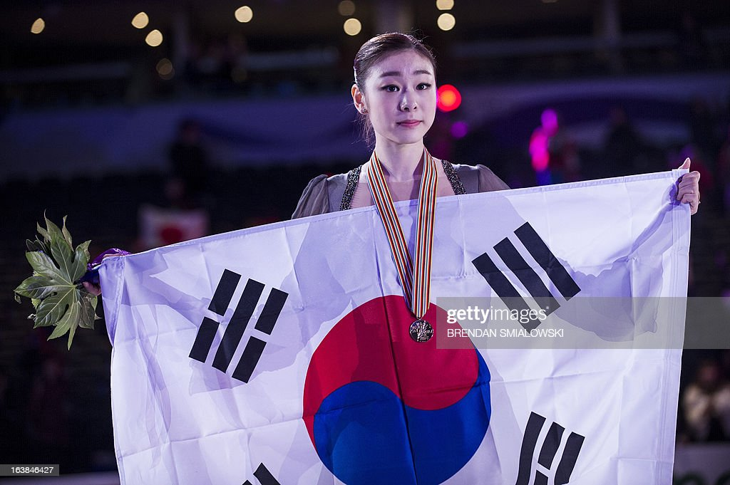 Gold medalist Kim Yu-na of South Korea holds the South Korean national flag during the victory ceremony for the dance competition at the 2013 World Figure Skating Championships in London, Ontario, March 16, 2013. Reigning Olympic champion Kim Yu-Na won the women's title at the World Figure Skating Championships, taking a runaway triumph in the free skate final. AFP PHOTO / Brendan SMIALOWSKI