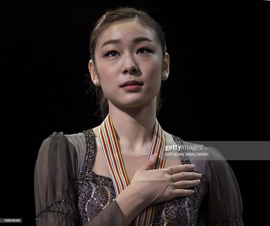 Gold medalist Kim Yu-Na of South Korea listens to her national anthem during the victory ceremony for the women's competition at the 2013 World Figure Skating Championships in London, Ontario, March 16, 2013. Reigning Olympic champion Kim Yu-Na won the women's title at the World Figure Skating Championships, taking a runaway triumph in the free skate final. AFP PHOTO / Brendan SMIALOWSKI