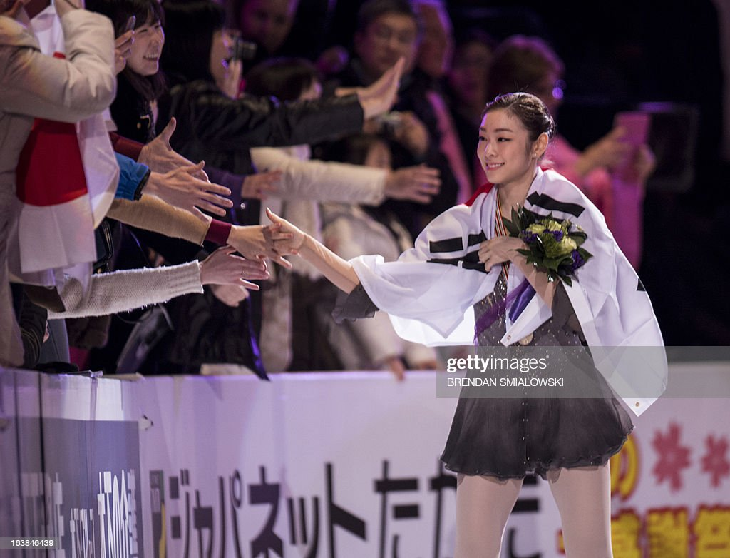 Gold medalist Kim Yu-na (R) of South Korea wears the South Korean national flag during the victory ceremony for the dance competition at the 2013 World Figure Skating Championships in London, Ontario, March 16, 2013. Reigning Olympic champion Kim Yu-Na won the women's title at the World Figure Skating Championships, taking a runaway triumph in the free skate final. AFP PHOTO / Brendan SMIALOWSKI