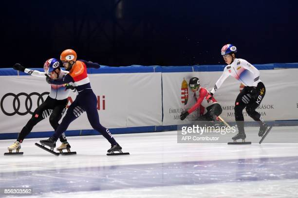 Gold medalist Korea's Lim Hyo Jun fights with Netherlands' Sjinkie Knegt in front of the finish line as Canada's Charle Cournoyer falls during the...