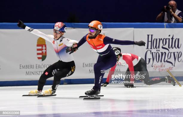 Gold medalist Korea's Lim Hyo Jun vies with Netherlands' Sjinkie Knegt in front of the finish line as Canada's Charle Cournoyer falls during the...
