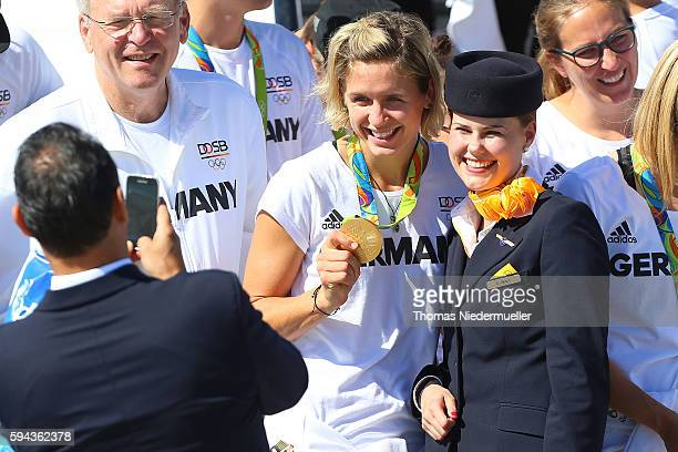 Gold medalist Laura Ludwig pose with a flight attendant during the arrival of German Summer Olympic Athletes from the Olympic Games in Rio at...