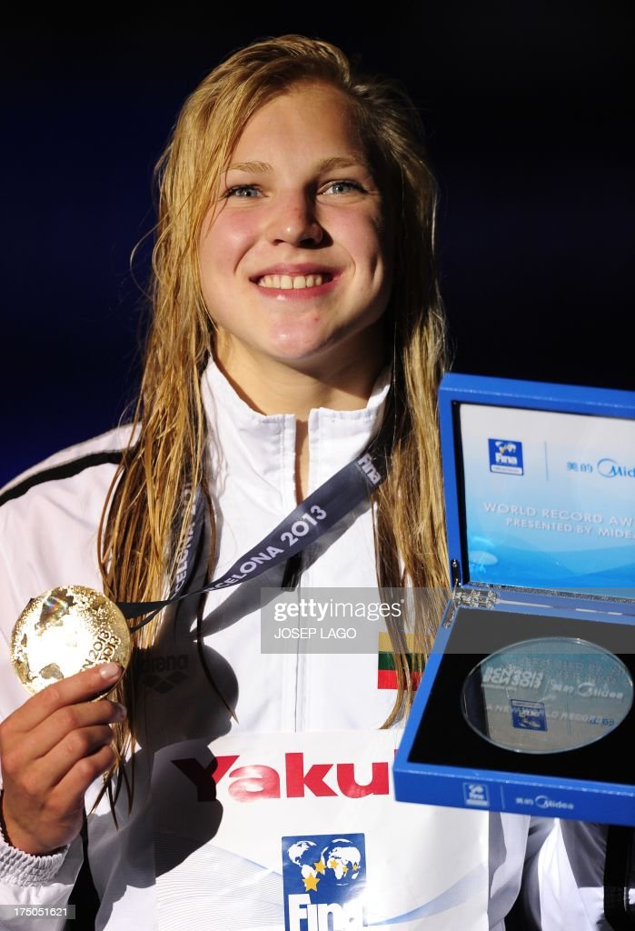 Gold medalist Lithuania's Ruta Meilutyte poses with her medal and the women's 100m breaststroke world record award during the award ceremony of the women's 100-metre breaststroke swimming event in the FINA World Championships at Palau Sant Jordi in Barcelona on July 30, 2013. Lithuania's Ruta Meilutyte broke the women's 100m breaststroke world record in the semi-finals of the event on July 29.