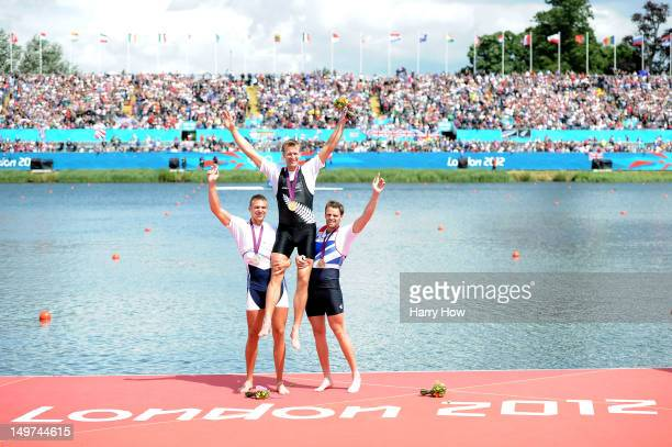 Gold medalist Mahe Drysdale of New Zealand is lifted on the shoulders of silver medalist Ondrej Synek of Czech Republic and bronze medalist Alan...