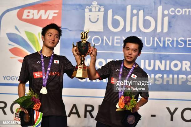 Gold medalist Mahiro Kaneko and Yunosuke Kubota of Japan celebrate on the podium with the trophy after beating Di Zijian and Wang Chang of China in...