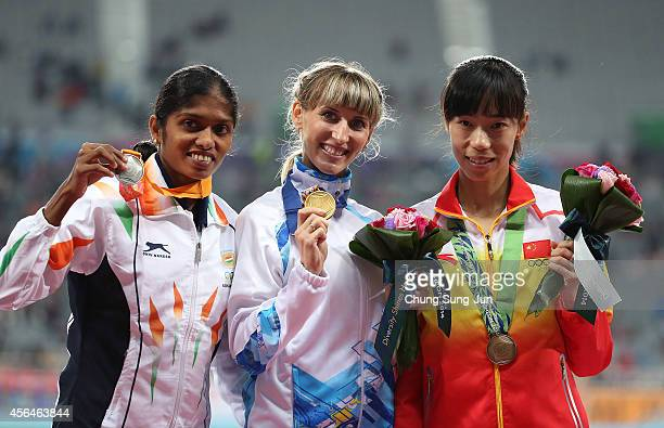 Gold medalist Margarita Mukasheva of Kazakhstan Silver medalist Tintu Lukka of India and Bronze medalist Zhao Jing of China pose after the medal...
