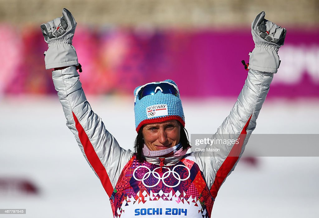 Gold medalist Marit Bjoergen of Norway celebrates on the podium during the flower ceremony for the Ladies' Skiathlon 7.5 km Classic + 7.5 km Free during day one of the Sochi 2014 Winter Olympics at Laura Cross-country Ski & Biathlon Center on February 8, 2014 in Sochi, Russia.