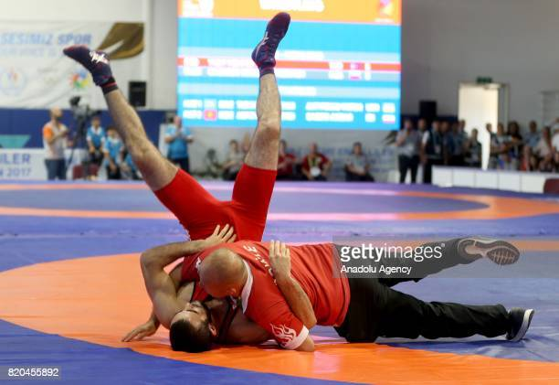 Gold medalist Mehmet Ali Yigit of Turkey celebrates with his trainer after winning against Kirill Andreevich Chulkov of Russia in men's 59 kg...
