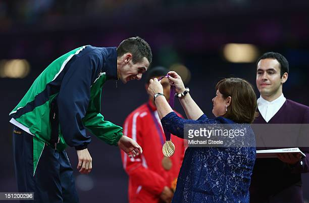 Gold medalist Michael Mckillop of Ireland is presented his medal by his mum Catherine McKillop during the medal ceremony for the Men's 1500m T37...