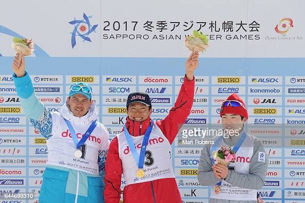 Gold medalist Mikito Tachizaki of Japan celebrates on the podium with siver medalist Yan Savitskiy of Kazakhstan and bronze medalist Yonggyu Kim of...