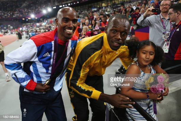 Gold medalist Mohamed Farah of Great Britain and his daughter Rihanna Farah pose with Gold medalist Usain Bolt of Jamaica on Day 15 of the London...