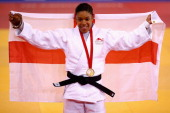 Gold medalist Nekoda Davis of England celebrates on the podium during the medal ceremony for the Women's 57kg l contest at SECC Precinct during day...