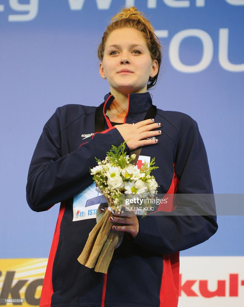 Gold medalist Olivia Smoliga (C) of USA, poses on the podium after winning the women`s 100m backstroke on December 13, 2012 during the FINA World Short Course Swimming Championships in Istanbul. AFP PHOTO/BULENT KILIC
