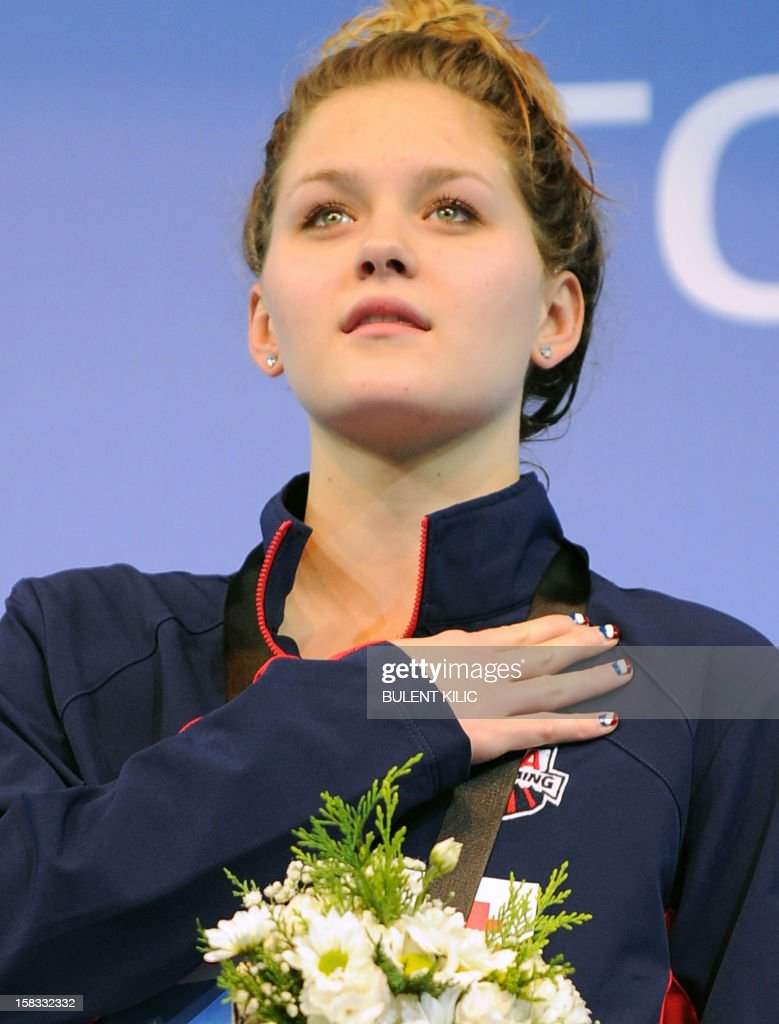 Gold medalist Olivia Smoliga (C) of USA, poses on the podium after winning the women`s 100m backstroke on December 13, 2012 during the FINA World Short Course Swimming Championships in Istanbul.