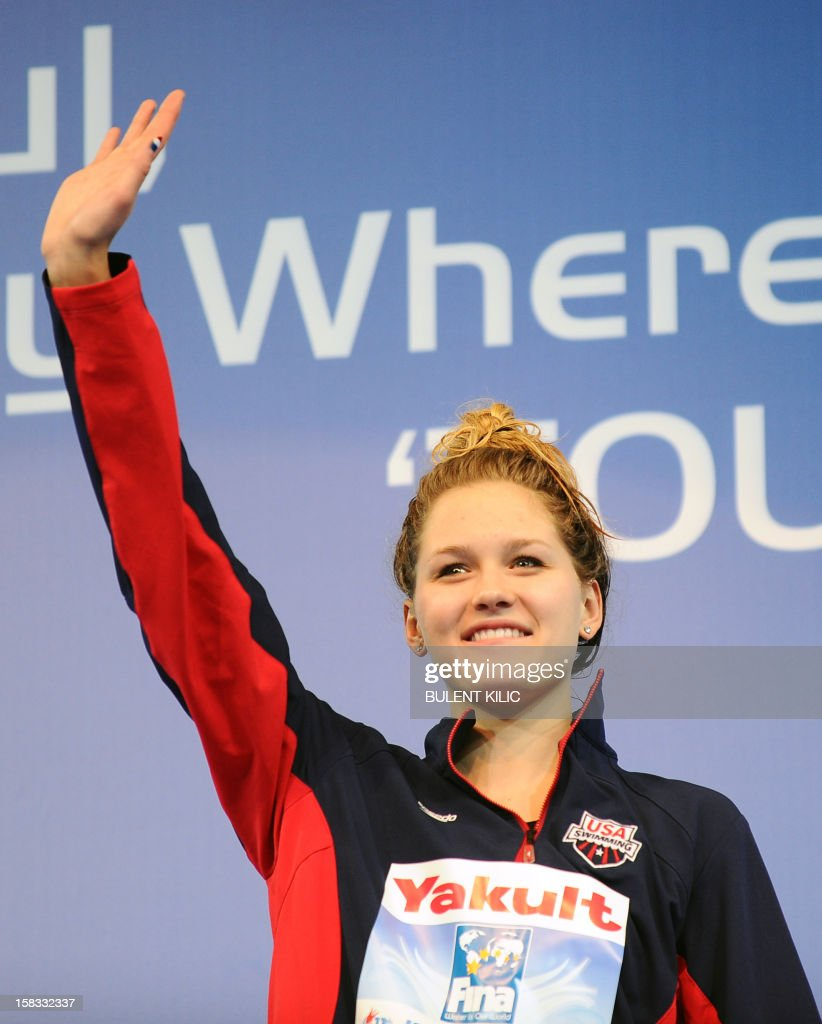 Gold medalist Olivia Smoliga (C) of USA, waves on the podium after winning the women`s 100m backstroke on December 13, 2012 during the FINA World Short Course Swimming Championships in Istanbul.