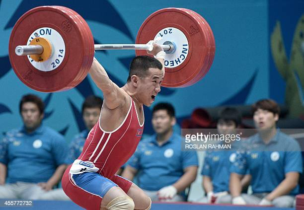 Gold medalist Om YunChol of North Korea attempts a lift in the men's 56kg weightlifting event during the 2014 Asian Games in Incheon on September 20...