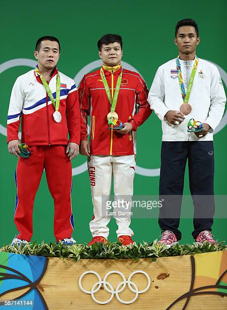 Gold medalist Qingquan Long of China silver medalist Yun Chol Om of North Korea and bronze medalist Sinphet Kruaithong of Thailand celebrate on the...