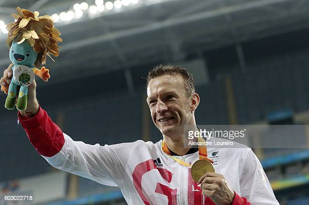Gold medalist Richard Whitehead of Great Britain celebrate on the podium at the medal ceremony for the Menâs 200m â T42 Final during day 4 of the Rio...
