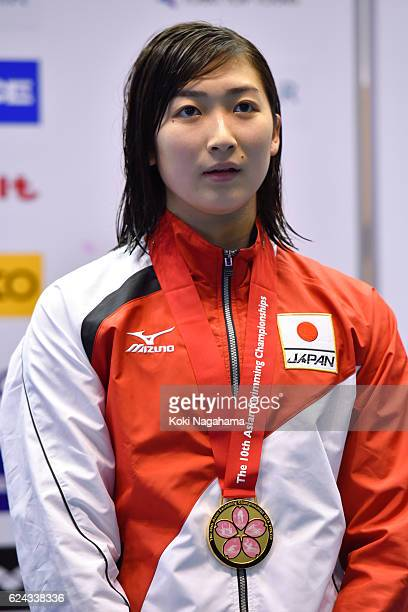 Gold medalist Rikako Ikee of Japan stands for her national anthem on the podium after Women's 100m butterfly final during the 10th Asian Swimming...