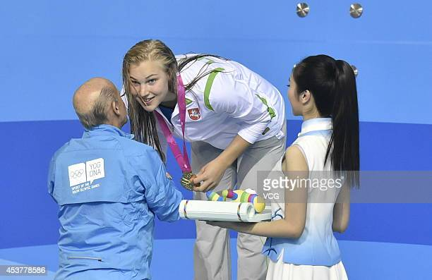Gold medalist Ruta Meilutyte of Lithuania celebrates on the podium after the Women's 50m Breaststroke final match on day two of the Nanjing 2014...