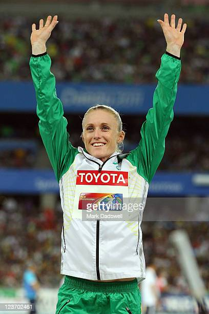 Gold medalist Sally Pearson of Australia salutes the crowd on the podium before receiving her medal for the women's 100 metres hurdles during day...