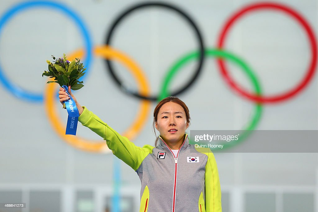 Gold medalist Sang Hwa Lee of South Korea celebrates on the podium during the flower ceremony for the Speed Skating Women's 500m Event during day 4 of the Sochi 2014 Winter Olympics at Adler Arena Skating Center on February 11, 2014 in Sochi, Russia.
