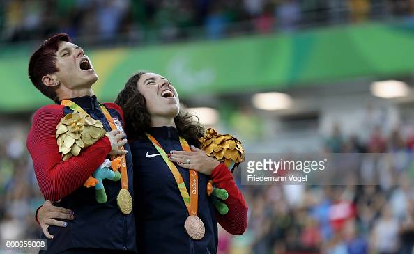 Gold medalist Shawn Morelli of the USA and bronze medalist Megan Fisher of the USA sing the national anthem on the podium at the medal ceremony for...